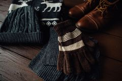 Male winter style on a brown wooden background. Winter brown shoes, grey sweater with deer, grey knitted scarf and hat and brown gloves. Top view Royalty Free Stock Image