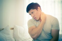 Male woke up with neck pain from sleeping. Male woke up having neck pain from sleeping Royalty Free Stock Image