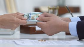 Male and woman pulling dollars, divorce policy and engagement ring on table. Stock footage stock video