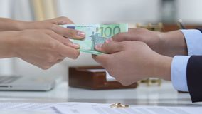 Male and woman pulling euros, divorce policy and engagement ring on table. Stock footage stock video footage
