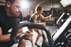 Male and woman taking rest after workout. Man and women leaning on cycling machines taking rest after riding workout in lighr spacious gym Royalty Free Stock Images