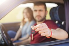Male and woman in car, focuse on keys. Blurred background. Man holds keys from vehicle, sells his automobile, advertises auto. Hor. Male and women in car, focuse Royalty Free Stock Image