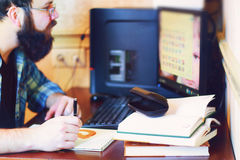 Male work computer pen write. Bearded man sitting at a table and working with a laptop Stock Photos