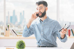Male at work talking on phone. Cheerful caucasian male sitting at workplace and talking on cellular phone Royalty Free Stock Photo