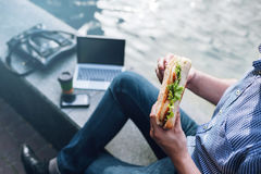 Male workaholic business lunch with junk food. Outdoors. Modern technology, unrecognizable businessman Royalty Free Stock Photos
