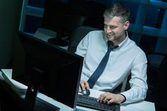 Male workaholic working at night. In the corporation Royalty Free Stock Images