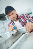 Male worker adjusting temperature water heater. Male worker adjusting temperature of water heater Royalty Free Stock Image