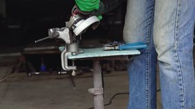 Male worker with angular grinding machine is cutting the metal. Slow motion stock footage