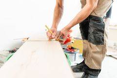 Male worker applies markings to the Board for cutting with a electrofret saw. installing new wooden laminate flooring. Male worker installing new wooden laminate royalty free stock images