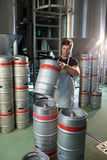Male worker arranging kegs. At warehouse Stock Photos