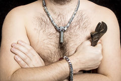 A male worker with a bare hairy-chested, wearing a necklace. Around the neck of the screws and bolt in the middle, in the hand is a wrench Stock Photography