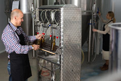 Male worker on beer brewery. Portrait of joyful mature male brewery worker operating bottling machinery on factory Stock Photo