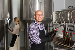 Male worker on beer brewery. Portrait of mature male brewery worker with bottling machinery on factory Stock Photography