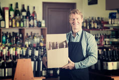 Male worker with big package in hands. Portrait of handsome male worker wearing uniform with big package in hands in winery Stock Photos