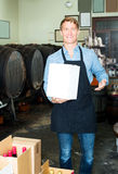 Male worker with big package in hands. Portrait of happy male worker wearing uniform with big package in hands in winery Royalty Free Stock Photography