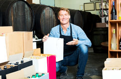 Male worker with big package in hands. Portrait of smiling male worker wearing uniform with big package in hands in winery Stock Photo