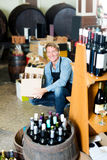 Male worker with big package in hands. Portrait of male worker wearing uniform with big package in hands in winery Stock Photography