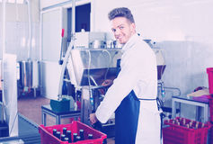 Male worker bottling wine with machine at sparkling wine factory. Diligent male worker bottling wine with machine at sparkling wine factory Royalty Free Stock Image