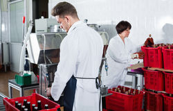 Male worker bottling wine with machine at sparkling wine factory. Friendly  male worker bottling wine with machine at sparkling wine factory Stock Images