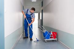 Male worker with broom cleaning office corridor Royalty Free Stock Photos