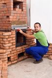 Male worker building a masonry heater royalty free stock photo