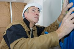 Male worker bundling pipework on interior building site royalty free stock photos
