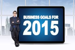 Male worker with business goals in office. Young businessman standing in the office while leaning on a board of business goals for number 2015 Stock Photography