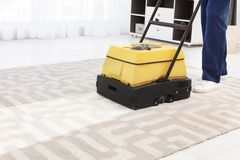 Male worker with carpet cleaner indoors. Closeup Stock Photo