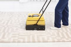 Male worker with carpet cleaner indoors,. Closeup Stock Image