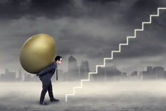 Male worker carry golden egg to the sky. Successful entrepreneur carrying golden egg to the sky through a staircase Royalty Free Stock Photo