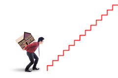 Male worker carrying house model. Young asian businessman carrying house model and walking upward on the stair. Property investment concept Royalty Free Stock Images