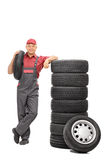 Male worker carrying a tire. Full length portrait of a male worker carrying a tire in one hand and leaning on a stack of tires isolated on white background Royalty Free Stock Photography