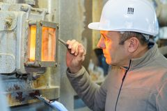 Male worker checking fire factory. Man stock image