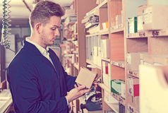 Male worker choosing items for work. Young  friendly male worker choosing items for work at workshop Royalty Free Stock Photography