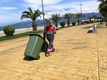 A male worker cleaner in uniform, a robe holding a spade on his shoulder and dragging a trash can on wheels on a tropical royalty free stock images