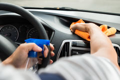 Male Worker Cleaning Car Dashboard. Cropped image of mature male worker cleaning car dashboard Royalty Free Stock Images