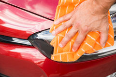 Male Worker Cleaning Car Headlight. Cropped image of male worker cleaning car headlight Stock Photography