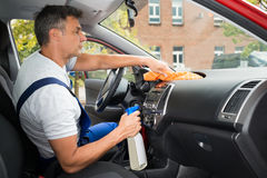 Male Worker Cleaning Car Interior. Side view of mature male worker cleaning car interior Royalty Free Stock Image