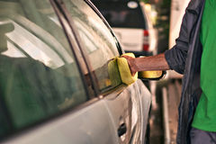 Male worker is cleaning a car with sponge. At service station Royalty Free Stock Images