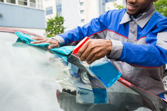 Male Worker Cleaning Car Windshield Stock Images