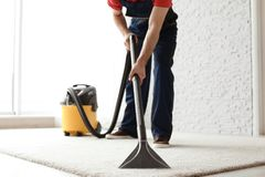 Male worker cleaning carpet with vacuum. Indoors royalty free stock photo