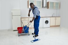 Male Worker Cleaning Floor. African Male Worker In Overall Cleaning Floor With Mop Stock Photos