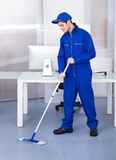 Male worker cleaning floor. Portrait Of A Male Worker Cleaning Floor With Mop Royalty Free Stock Image