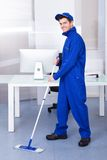 Male worker cleaning floor. Portrait Of A Male Worker Cleaning Floor With Mop Royalty Free Stock Photos