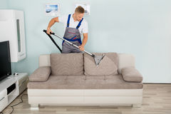 Male Worker Cleaning Sofa With Vacuum Cleaner Stock Photography
