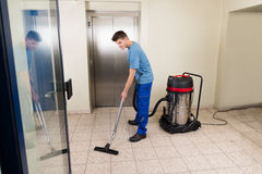 Male Worker Cleaning With Vacuum Cleaner Royalty Free Stock Photo