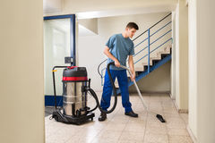 Male Worker Cleaning With Vacuum Cleaner. Happy Male Worker Cleaning Floor With Vacuum Cleaner Appliance Stock Image