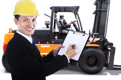 Male worker with clipboard and forklift. Businessman showing a clipboard while smiling at the camera with a forklift on the background Stock Photo
