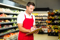 Male worker with clipboard. In grocery store Royalty Free Stock Photo