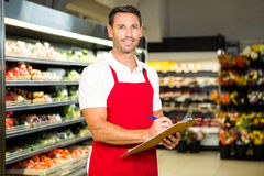 Male worker with clipboard. In grocery store Royalty Free Stock Photography